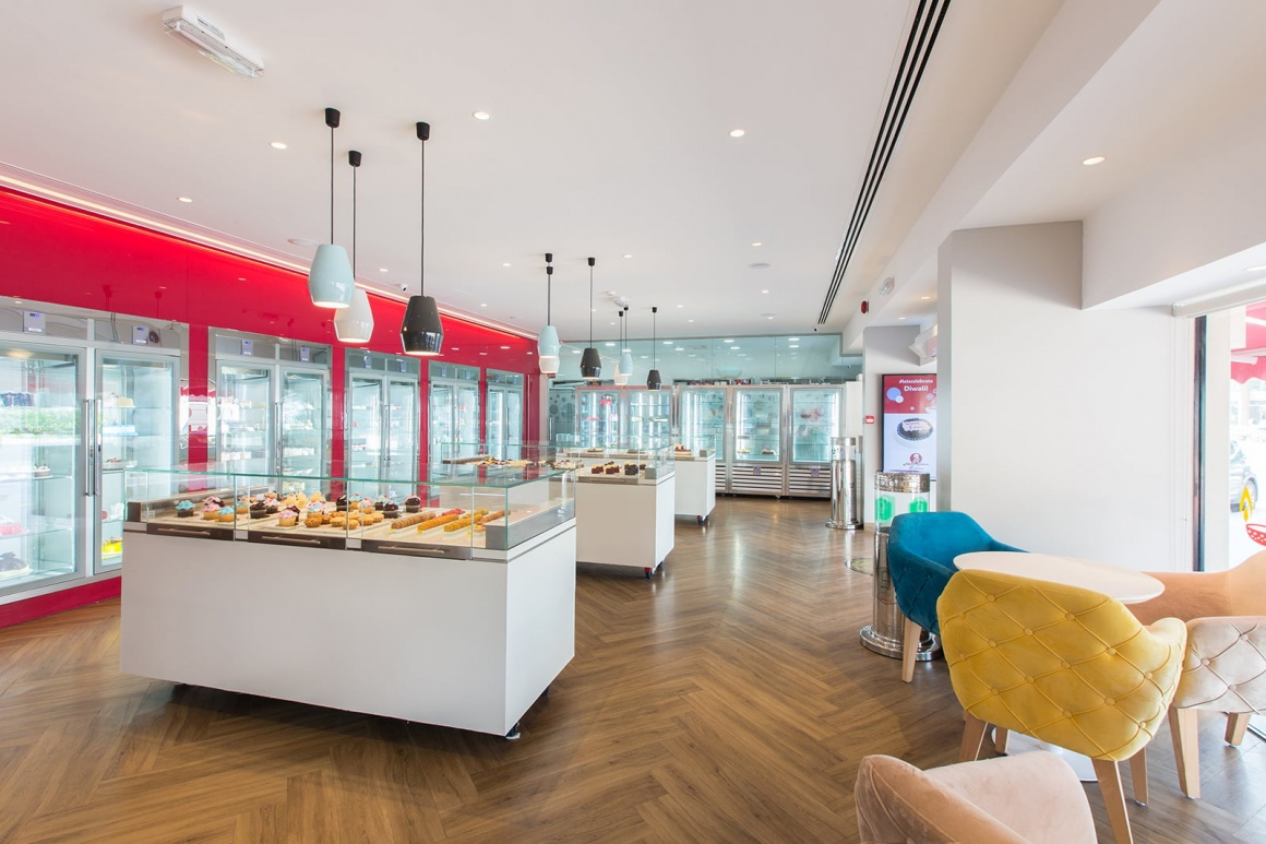 Photo: Modern bakery with counters, refrigerated shelves and seating areas;...