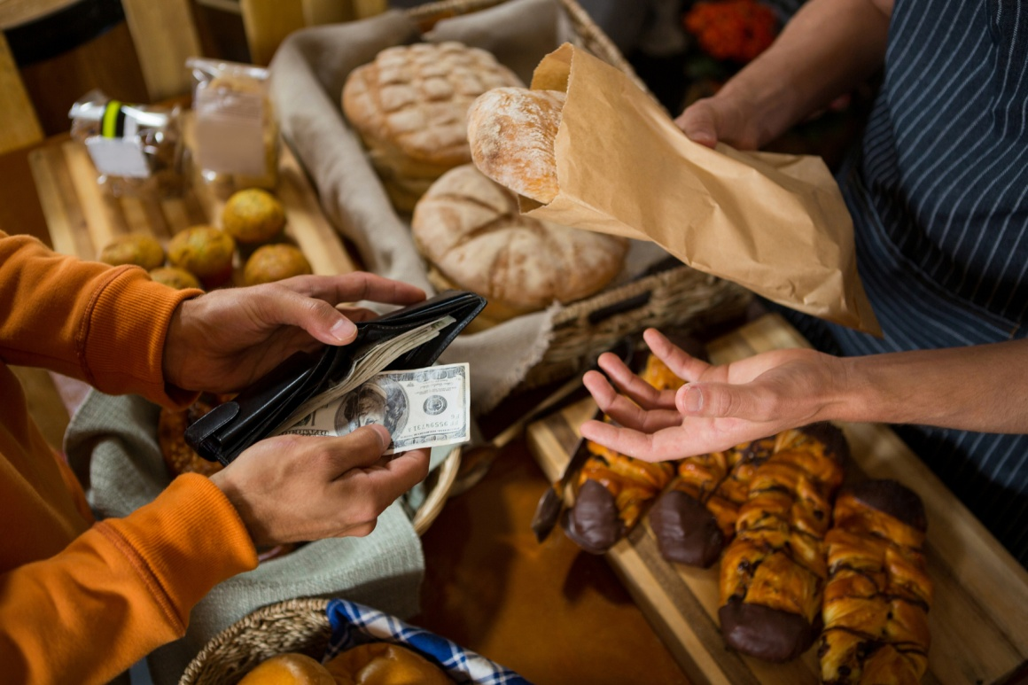 Photo: Person paying in cash in a bakery; copyright: panthermedia.net /...