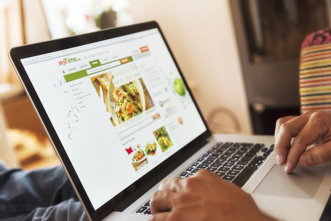 Photo: Person surfing on a laptop at the online supermarket myTime.de;...