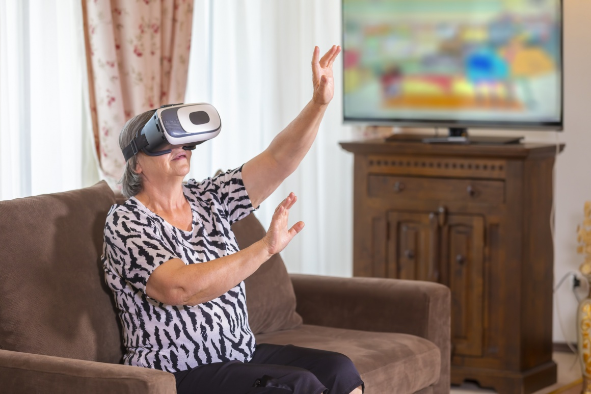 Older woman with VR glasses at home on the armchair; copyright:...