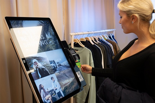 Woman using a touch screen in a store; copyright: Elo Touch Systems...