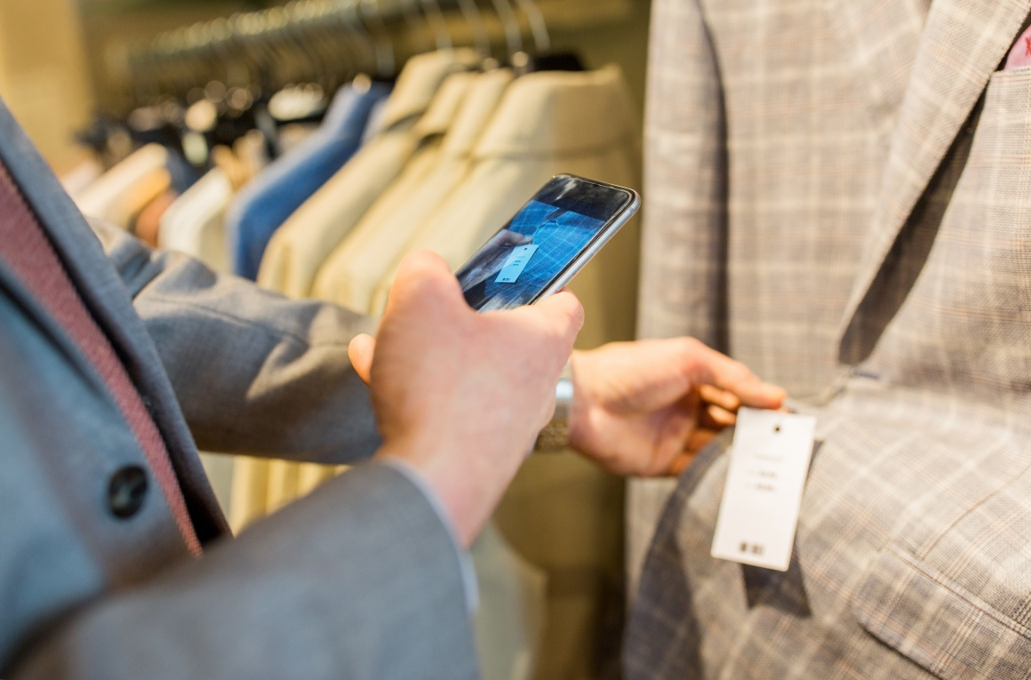 Person photographs price tag on jacket with smartphone; copyright:...