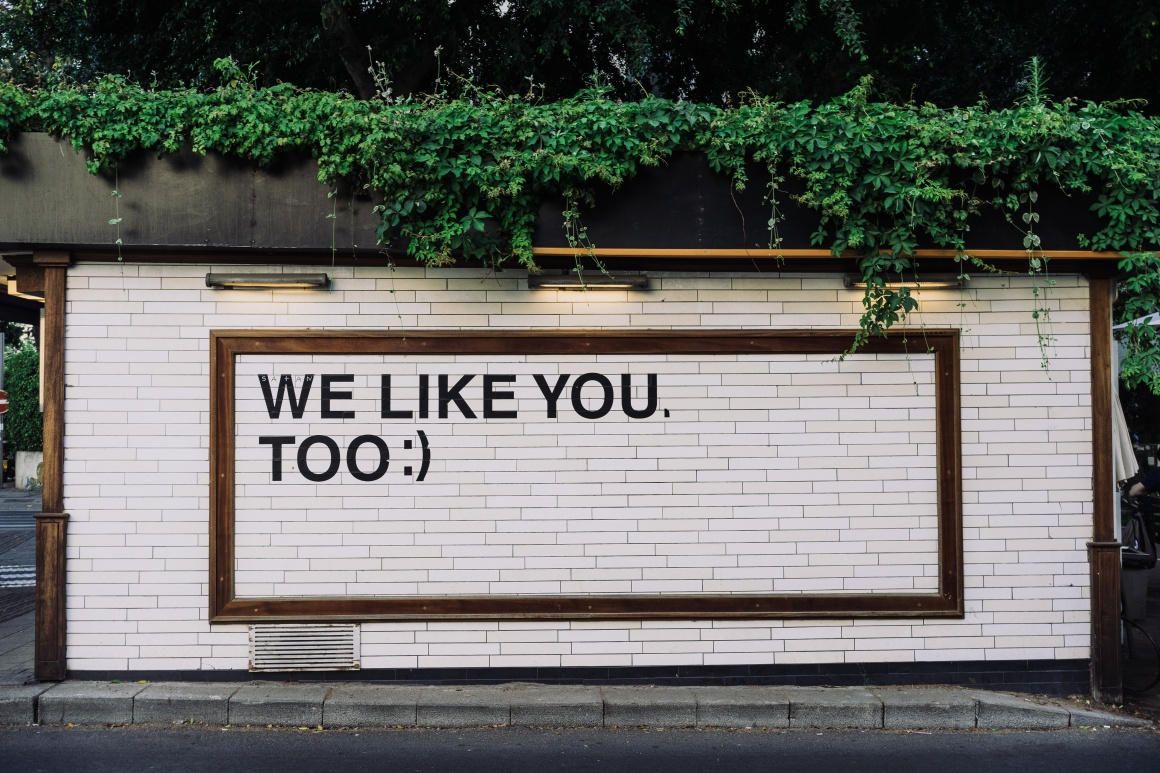Sign on a wall with text we like you too; Copyright: Adam Jang/Unsplash...