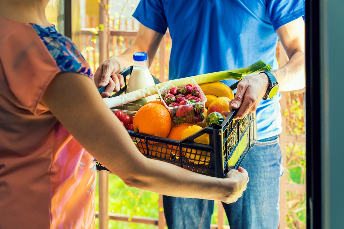 Delivery man hands over basket with groceries to woman at her door; copyright:...