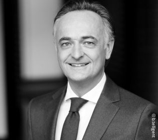 Black and white picture of a smiling man in a suit....