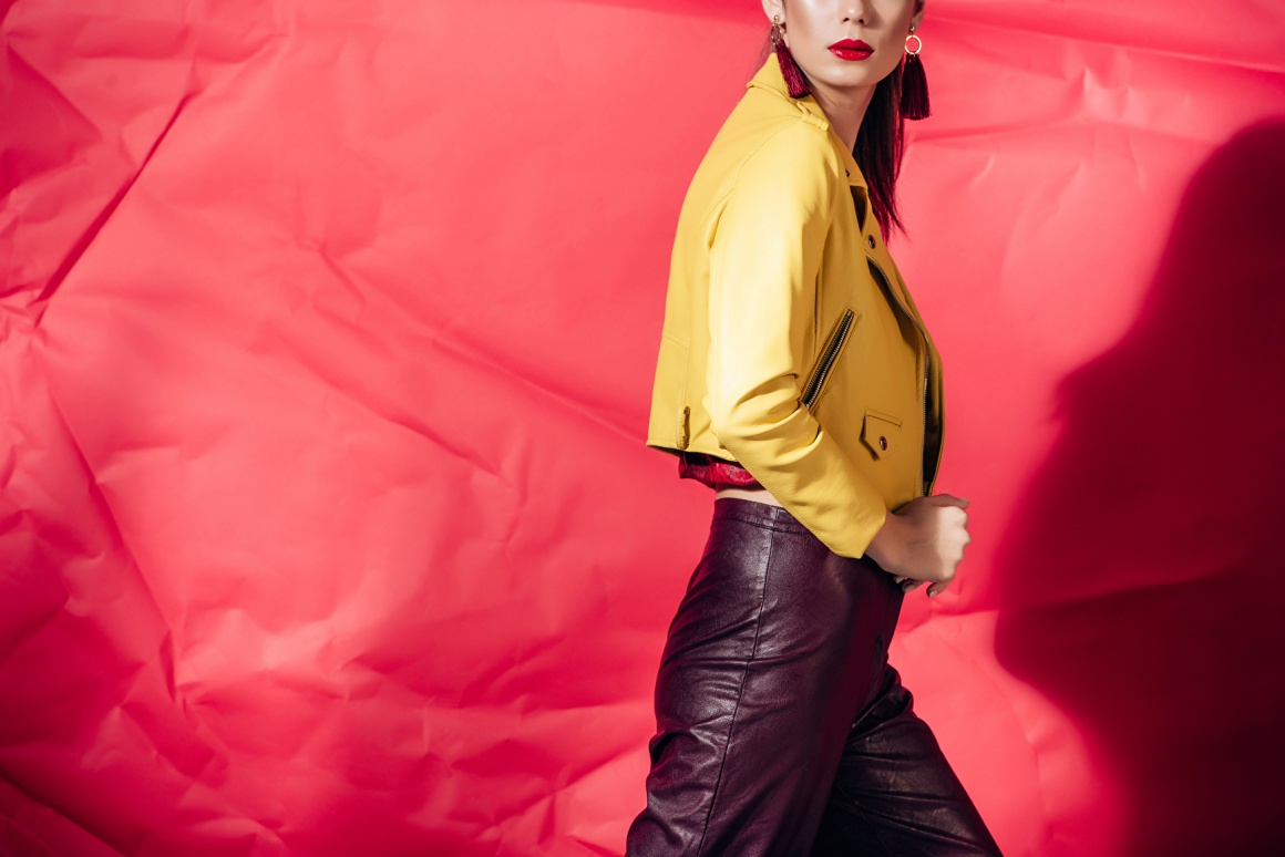 Woman wearing and showcasing a yellow leather jacket in front of a red...