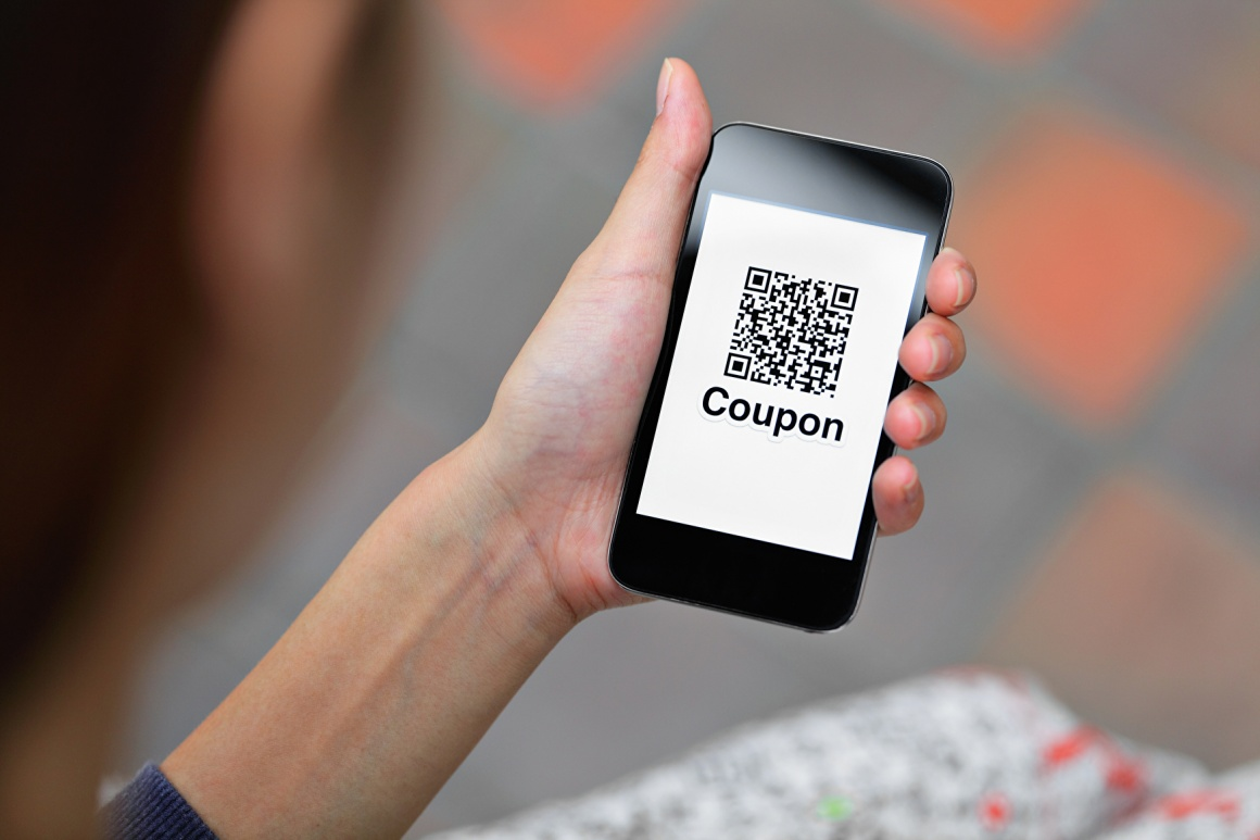 Person holding smartphone with QR code and Coupon on display...