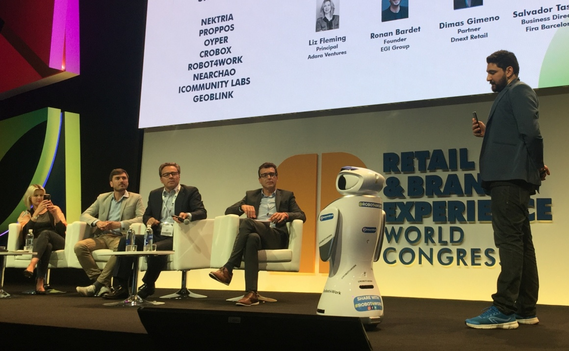 Five people on a stage in front of a big screen with a small humanoid robot;...