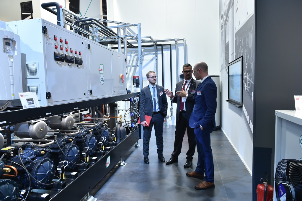 Men standing in front of refrigeration system