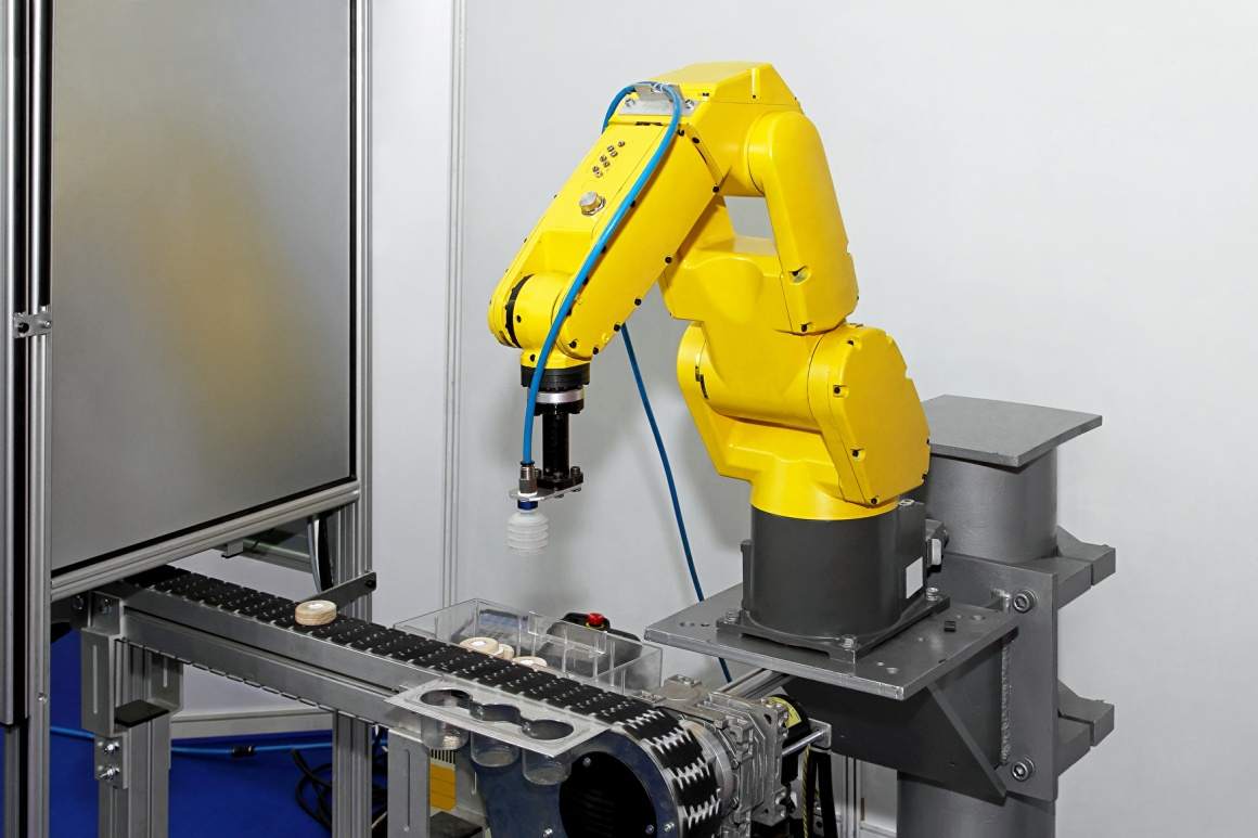 Yellow robot arm in an industrial production plant; copyright:...