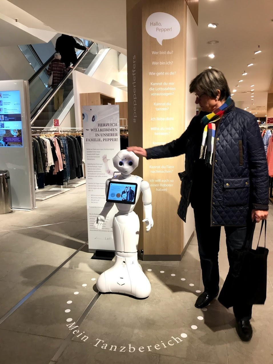 A customer in a fashion store strokes the white little robots head; copyright:...