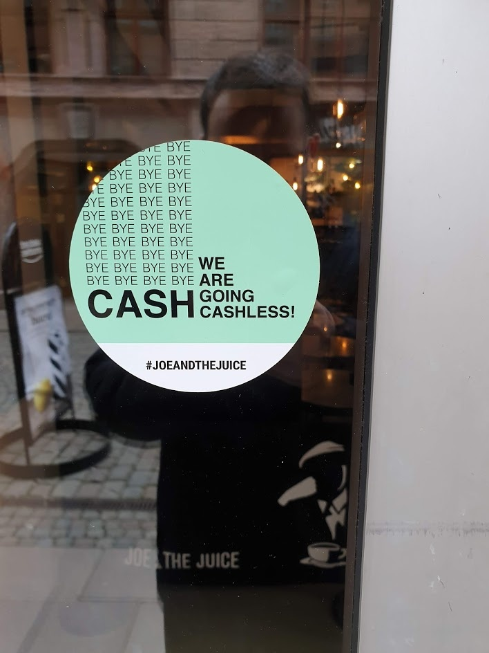 Sign on a glass door with the inscription We are going cashless....