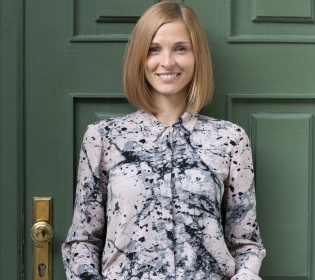 Blonde woman in blouse with flower patterns in front of dark green door smiling...