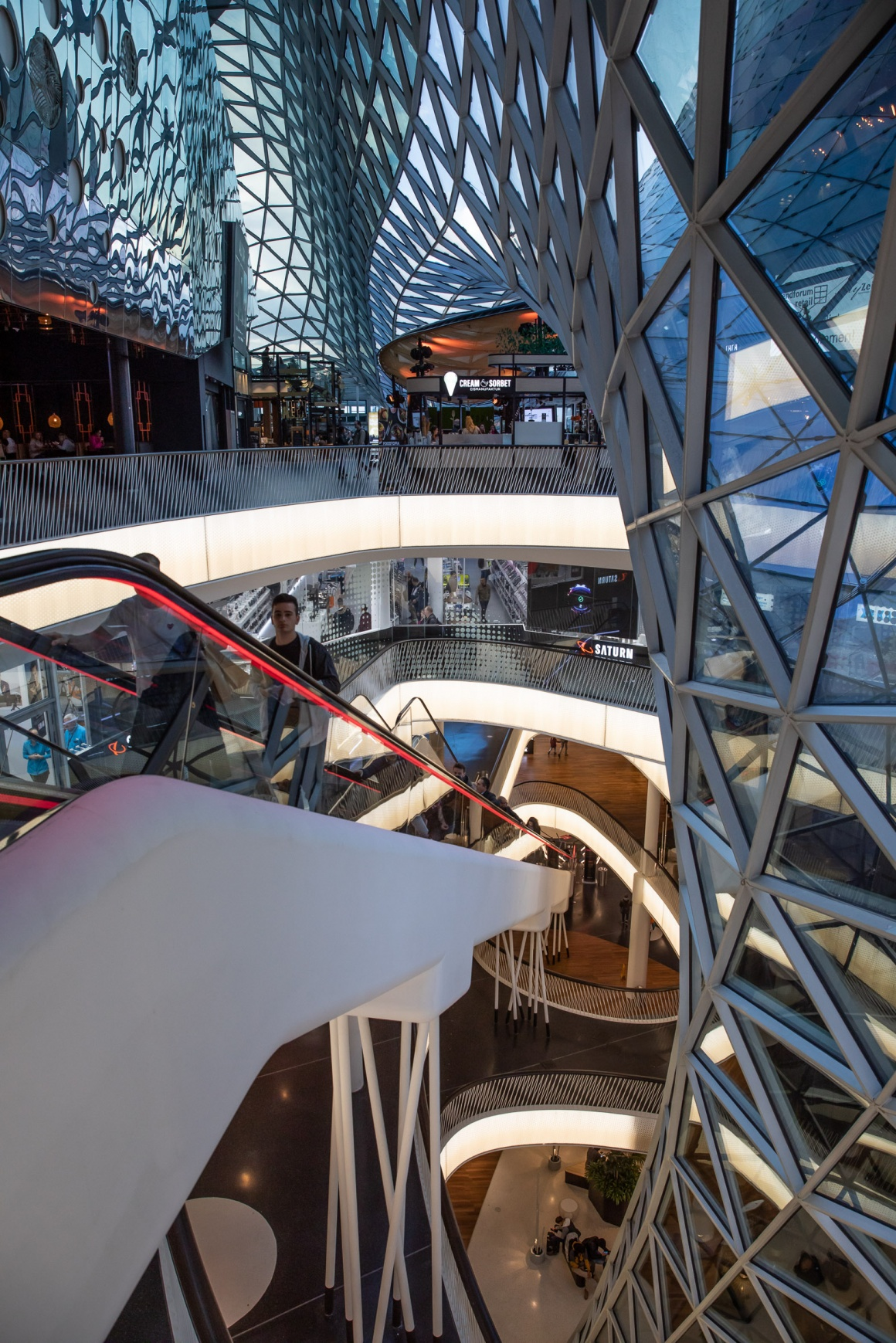 View into a shopping mall with several floors and elevators and glass walls...