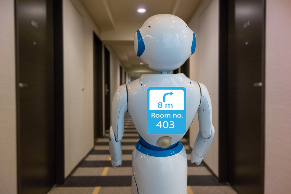 A white humanoid robot with a screen in the corridor of a hotel...