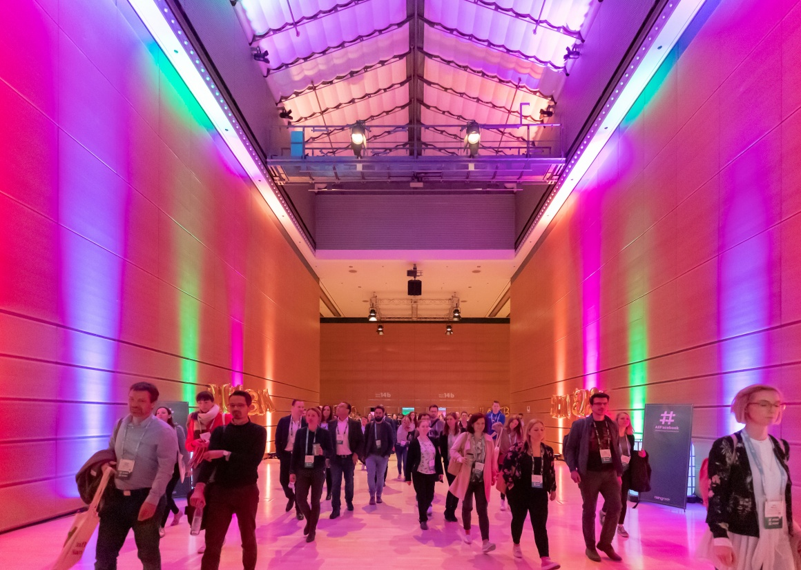 People walking through a colorfully lit corridor