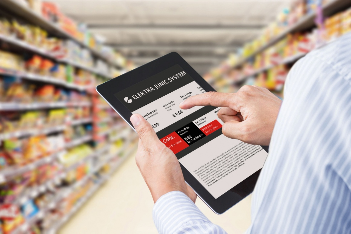 Person operates a tablet in a supermarket between shelves...