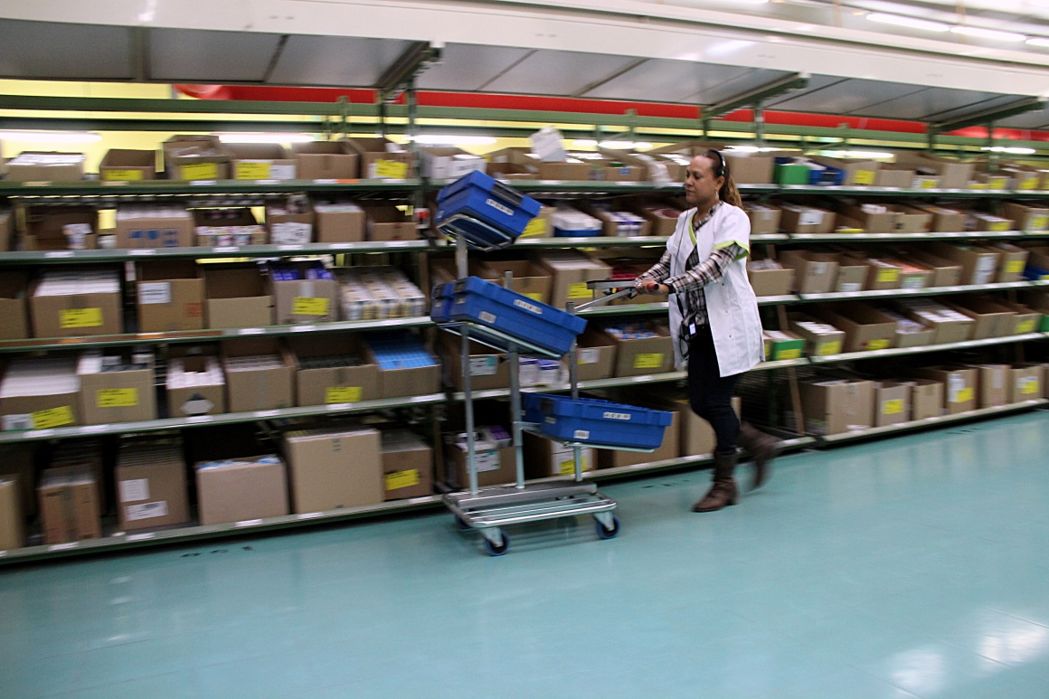 A woman passes a shelf with a multi-level trolley