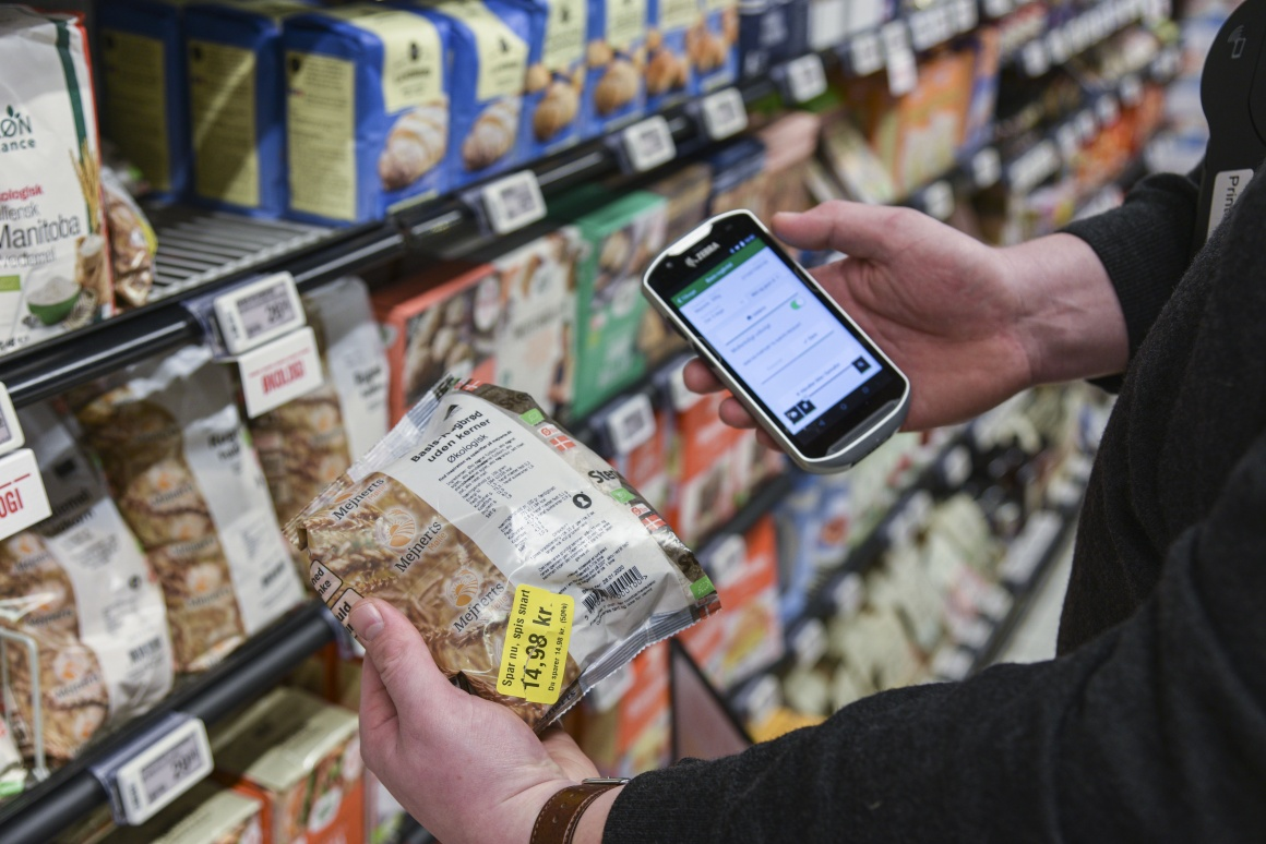 Person holding smartphone and product with discount label in a supermarket...
