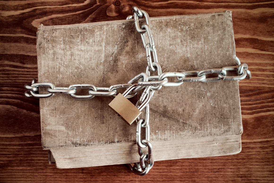 An old book locked with a chain and a padlock.