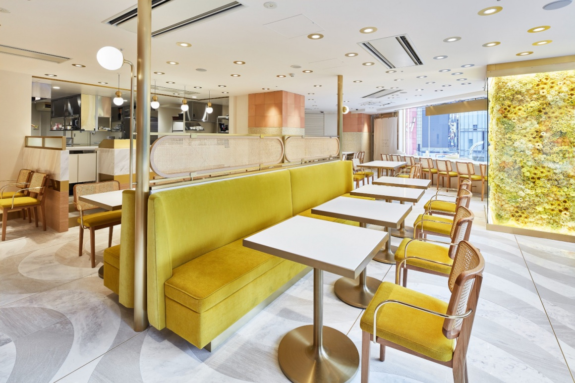 a view into a modern designed café with tables and chairs with yellow colours...