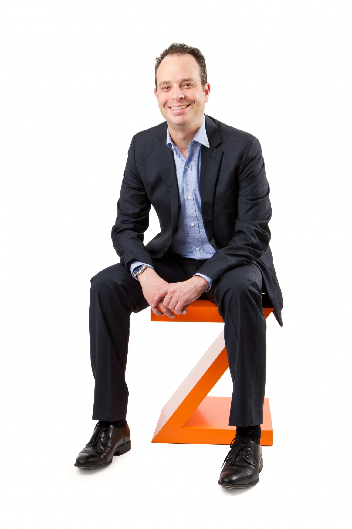 Man sitting on big orange Z against white background....