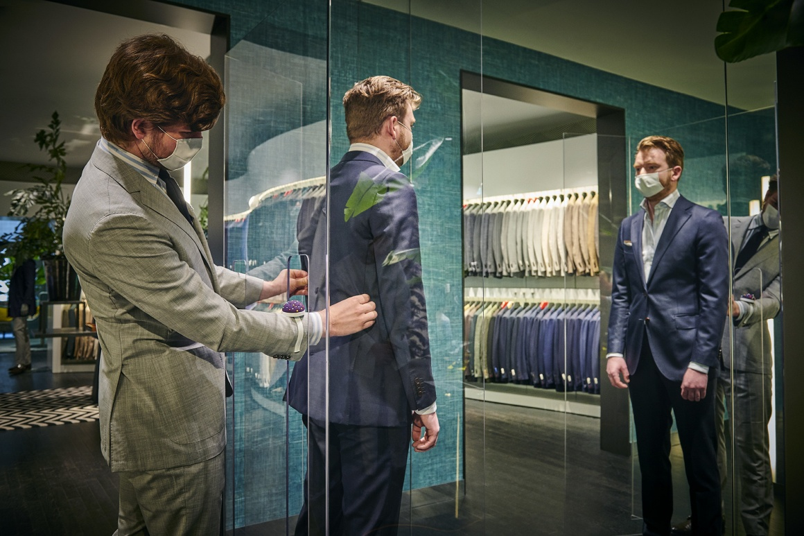 A tailor works on a suit a man inside a glass box is wearing...