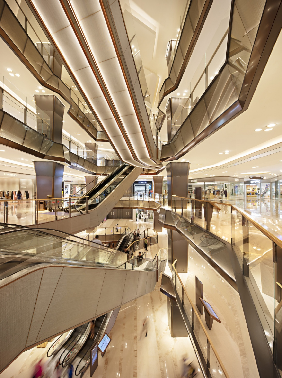 The interior of a shopping center with modern design and escalators...