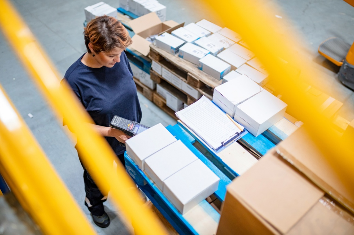 A woman working in a warehouse scanning packages