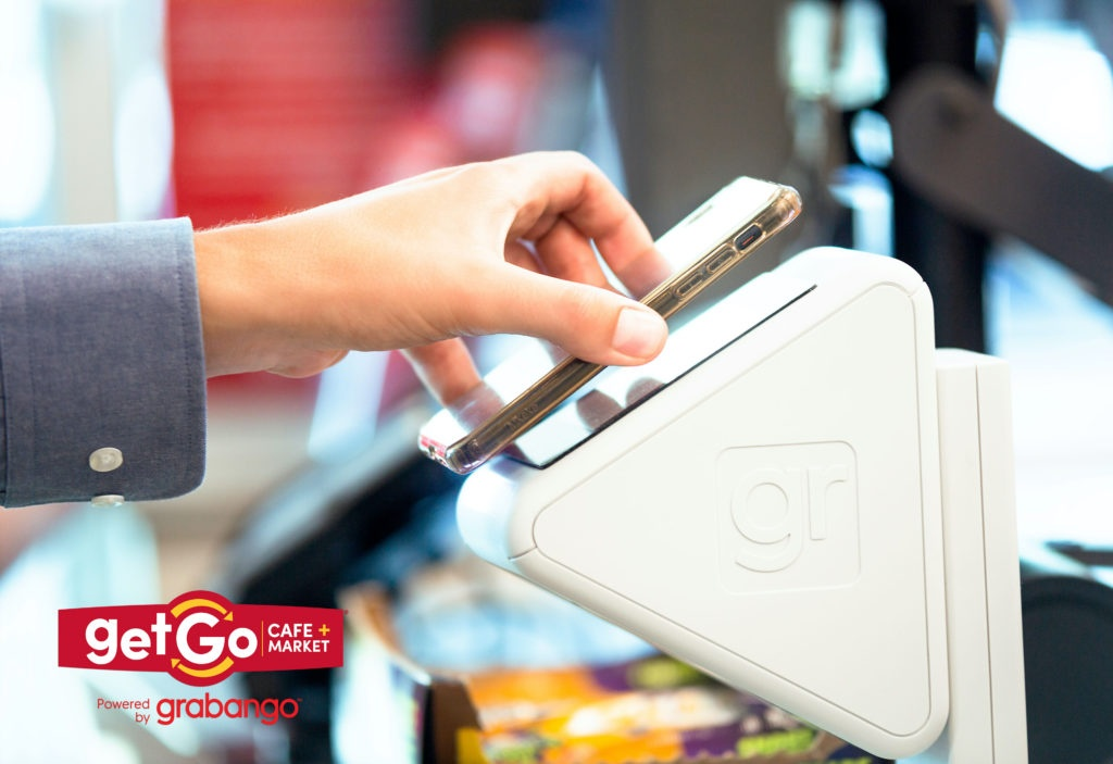 A hand holding a smartphone to a checkout device