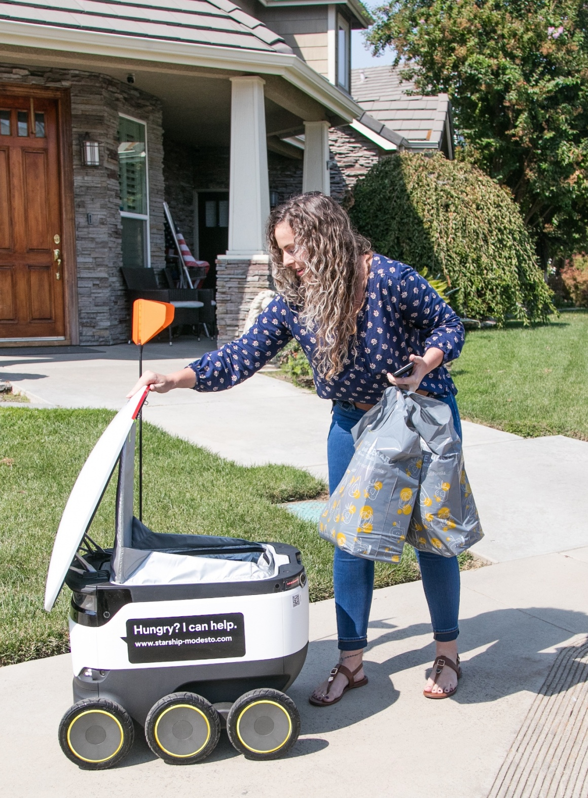 A woman is taking shopping bags from a delivery robot...