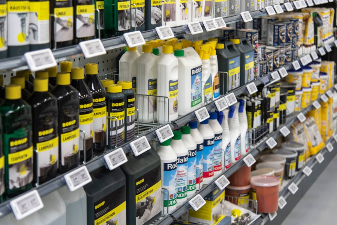 A shelf in a hardware store with products in bottles and electronic price tags...