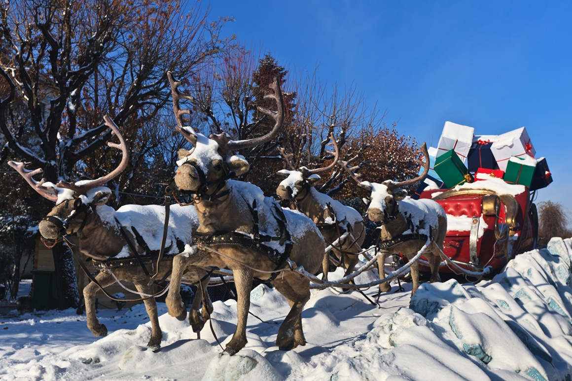 reindeer pull a carriage full of huge gifts through the snow...