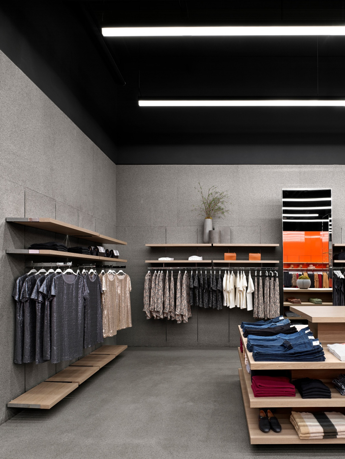 Interior of a flagship fashion store with grey walls and floor...