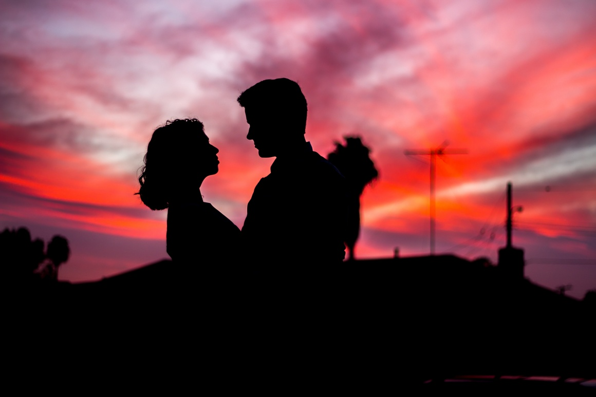 The dark silhouettes of a woman and a man in front of a red sunset...