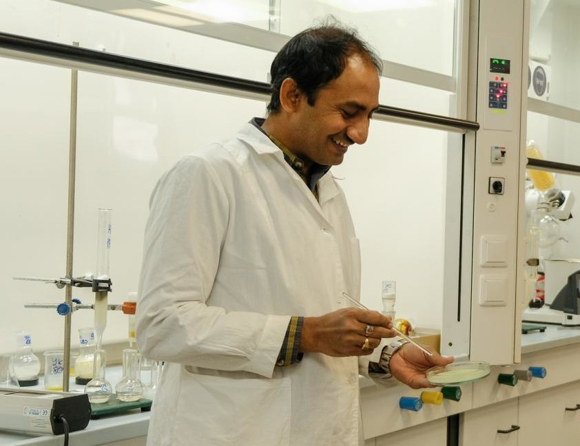 A scientist in a laboratory holding a Petri dish and a pipette...