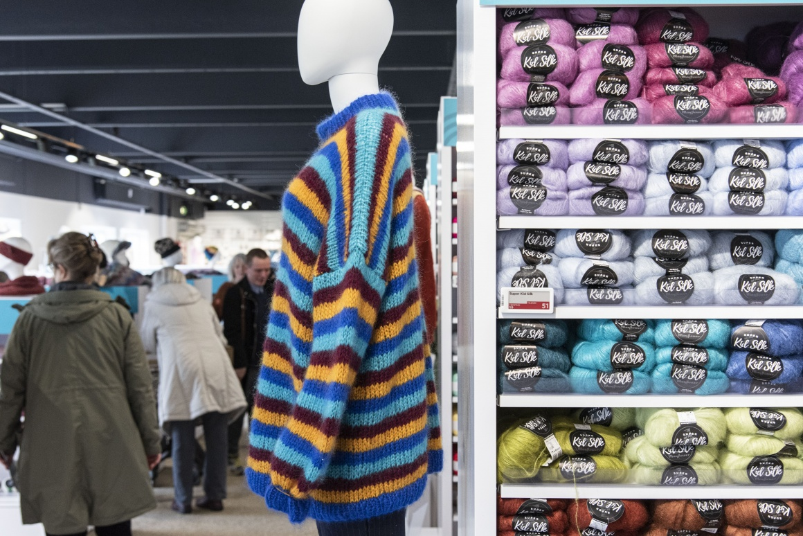 A mannequin with colorful sweater next to a shelf with wool...