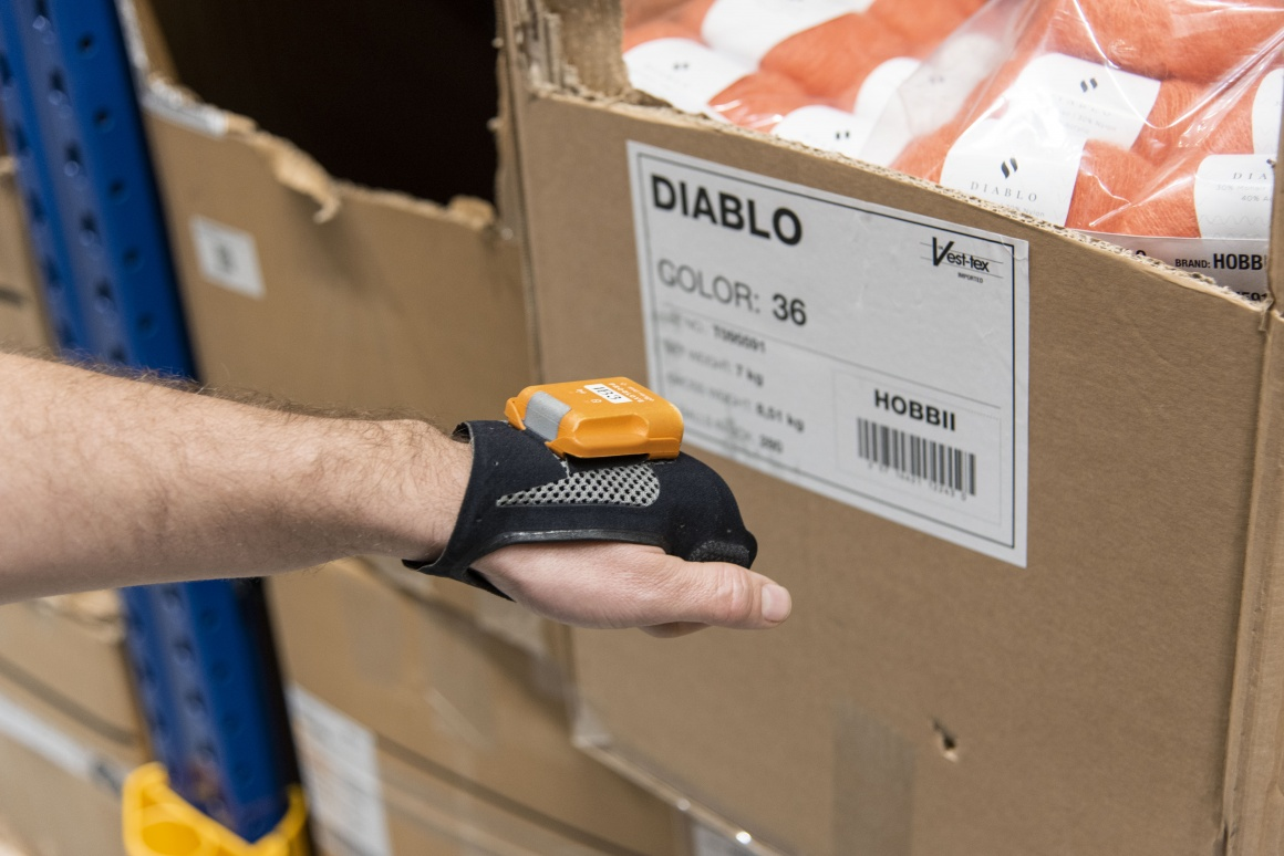 Shows the hand of a worker scanning a product package with a hands-free scanner...